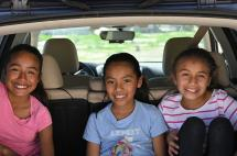 Three children smiling in a car